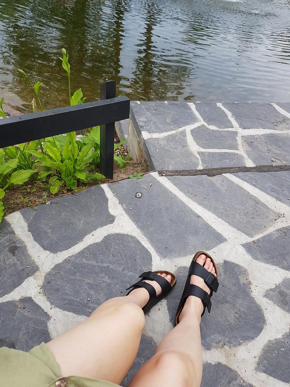 Kuvassa olen lammen rannalla ja jaloissani on juuri huolletut Birkenstock-sandaalini.