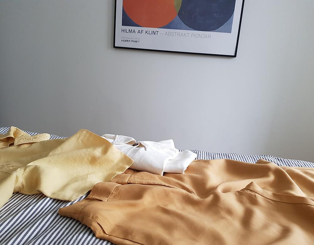 Kuvassa sängynpäädyllä valko harmaa raidallisen lakanan päällä silitettyjä kirpparilöytöjä: vaalean oranssit housut, vaaleankeltainen paita ja valkoinen kauluspaita. Tasutalla näkyy Hilma af Klintin maaluaksen julistetaulu.