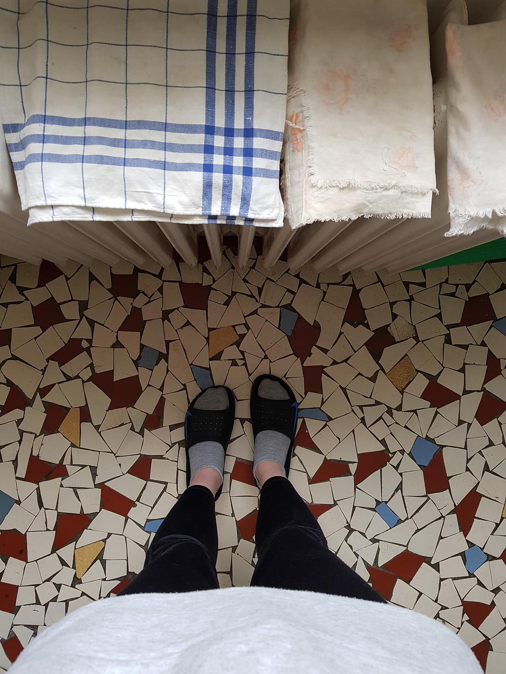 Ylhäältäpäin otettu kuva jaloistani ja patterista. Patterin päällä kuivuu keittiöpyyhkeitä. Päälläni on harmaa kollari, mustat legginssit ja tohvelit. Lattia on mosaiikkimainen koostuen valkoisista, tiilenvärisistä ja turkooseista paloista.