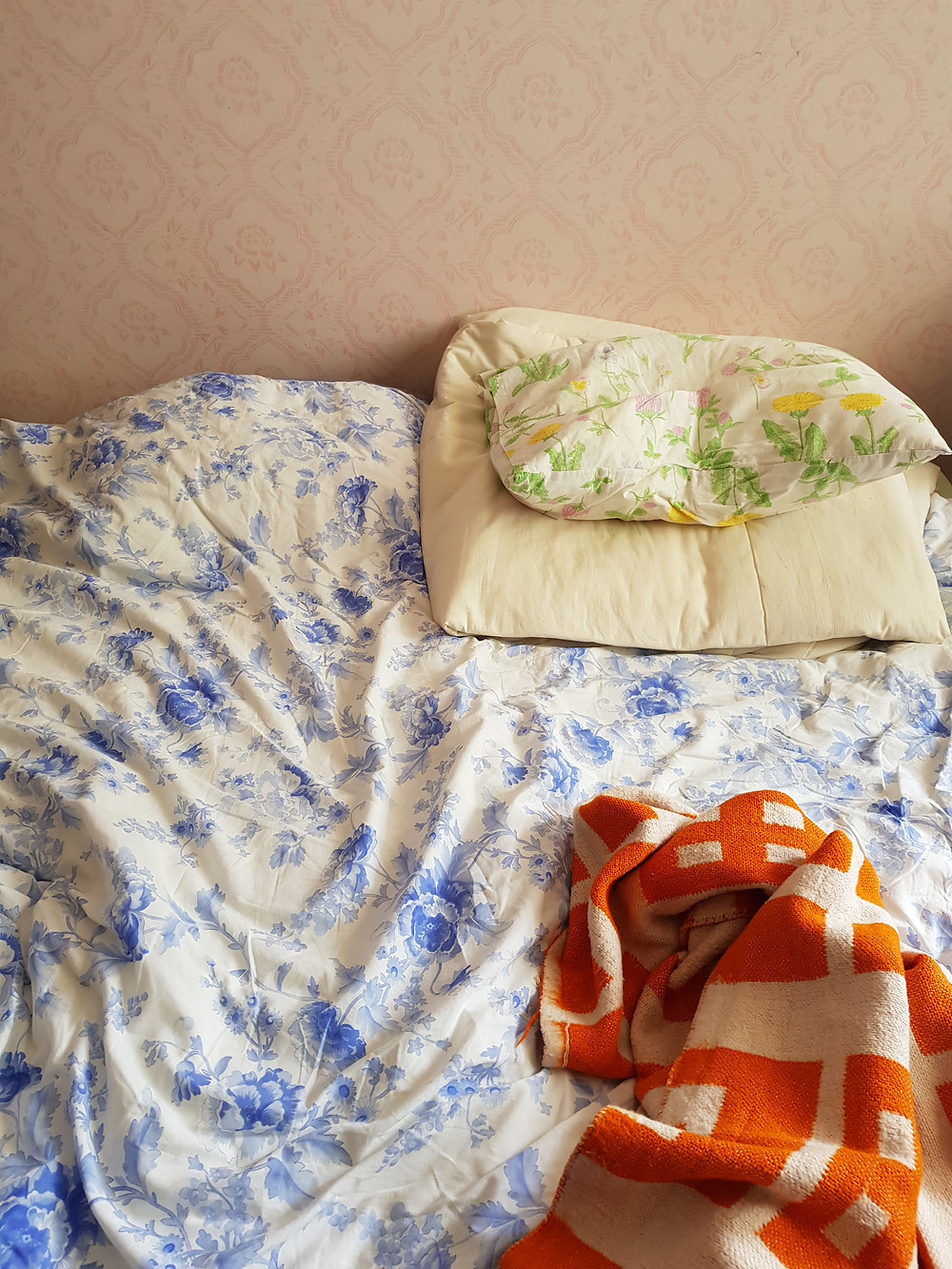 Kuva sängystä, jossa on ryppyinen sinivalkokukallinen peitto, oranssivalkoinen viltti ja vihreäkukallinen tyyny. Taustalla seinä, jossa vanhaa tapettia.