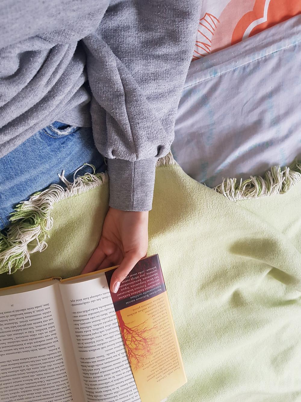 Ylhäältäpäin otettu kuva kädestäni ja kirjasta, jota luen (Marilynne Robinsonin Gilead). Minulla on päällä harmaa kollari ja farkut ja olen peittäytynyt vihreään vilttiin. Punakuvioinen retrotyynynpäällinen näkyy kuvan nurkassa.