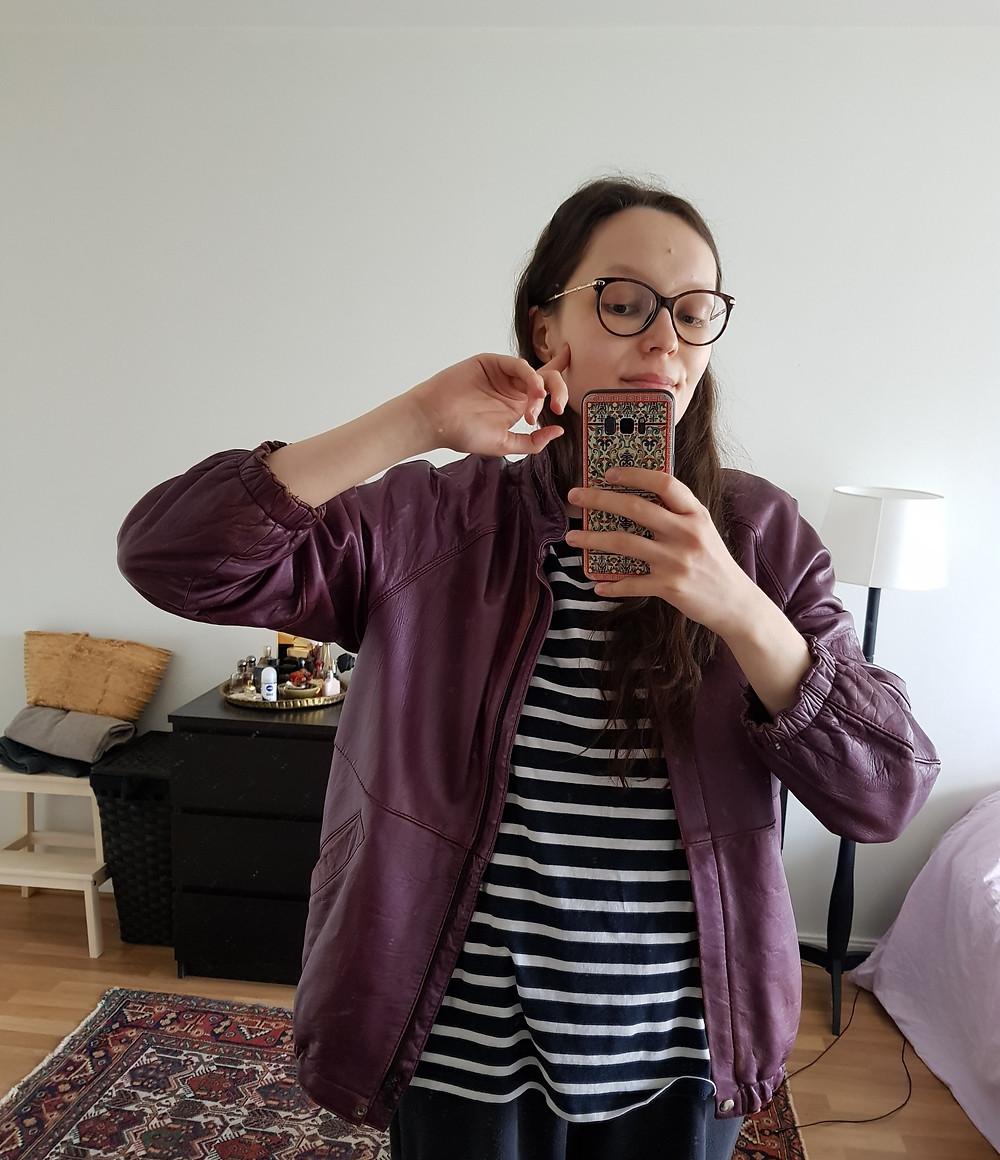 Olen ottanut kuvan peilin kautta, minulla on nahkatakki päällä, tummansininen ja valkoinen raidallinen t-paita ja kotihousut jalassa.
