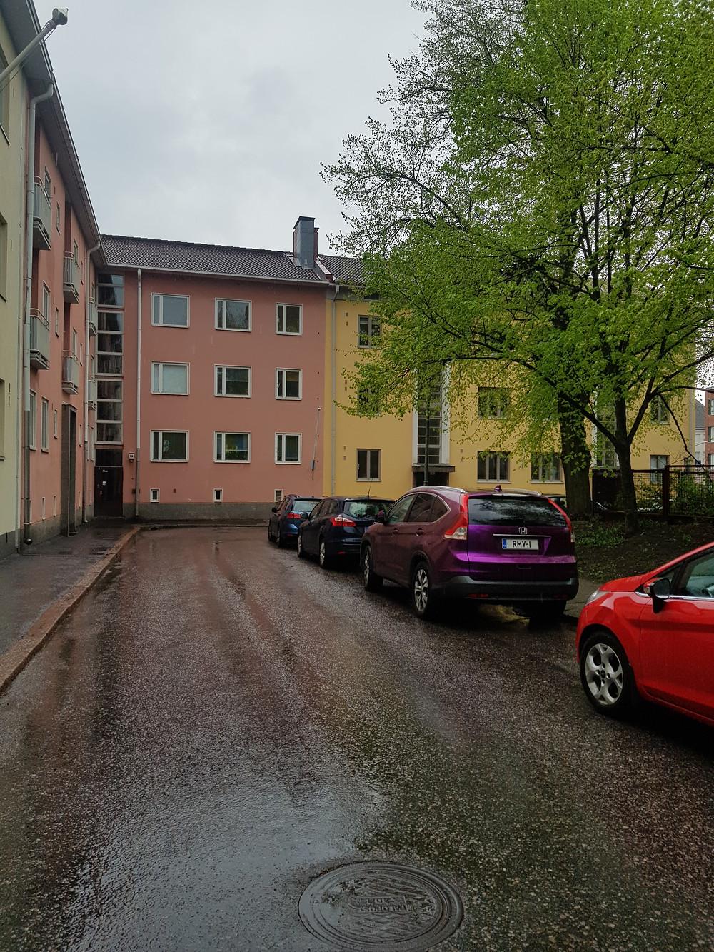Kuvassa on vihreä, punainen ja keltainen kerrostalon seinämä, sateen jälkeinen märkä asfaltti ja värikkäitä autoja tiensivuun parkkeerattuna.
