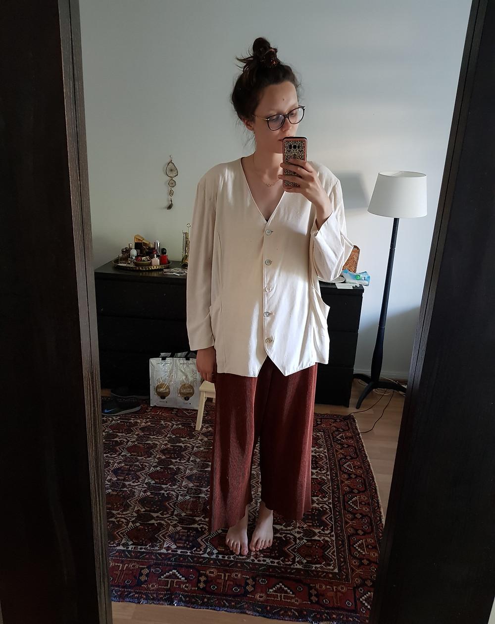Seison peilini edessä, tukkani on nutturalla ja päälläni on ruosteenoranssit leveät housut ja valkoinen silkkijakku.