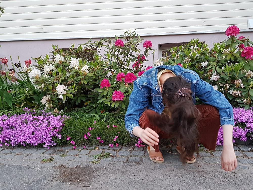 Olen kuvassa kyykyssä, pää alaspäin käännettynä ja hiukseni osuvat melkein maahan. Takanani on liloja, valkoisia ja pinkkejä kukkia ja omakotitalon puuseinä.