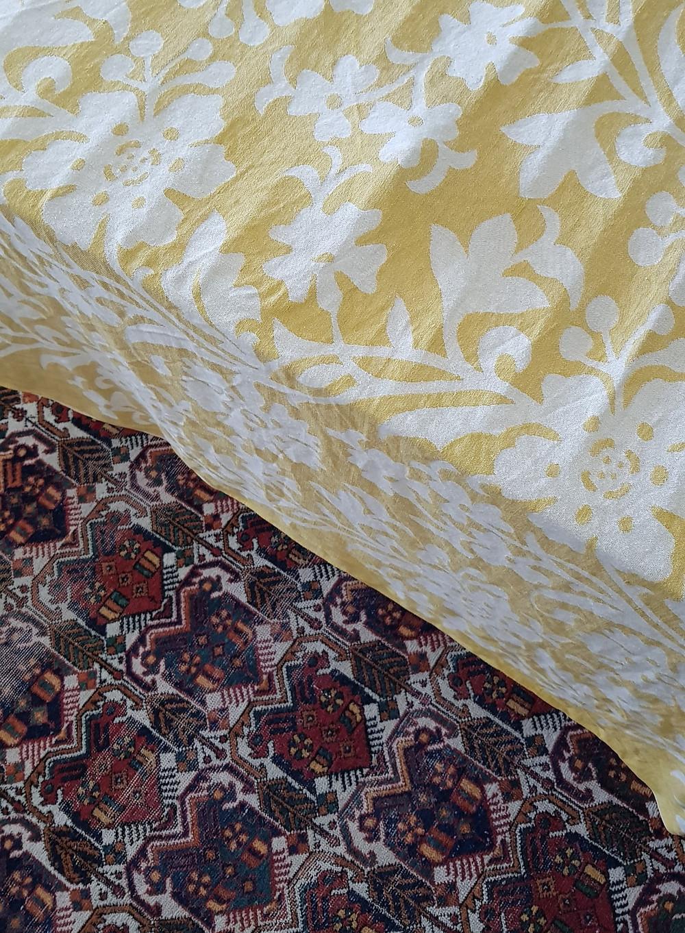 Kuvassa näkyy uusi keltainen pöytäliina valkoisilla kukilla kuivumassa kuivaustelineessä. Kuva on otettu ylhäältä päin ja taustalla näkyy punainen itämainen matto.
