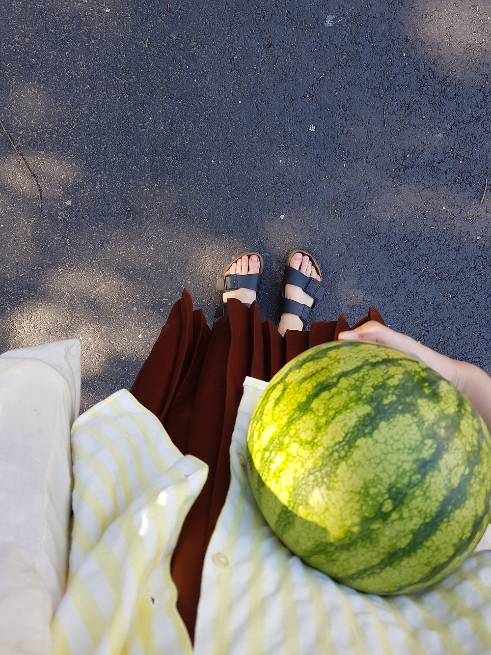 Olen ottanut kuvan itse ylhäältä alaspäin ja kuvassa näkyvät varpaani, hame ja paita sekä sylissä kantamani vesimeloni.