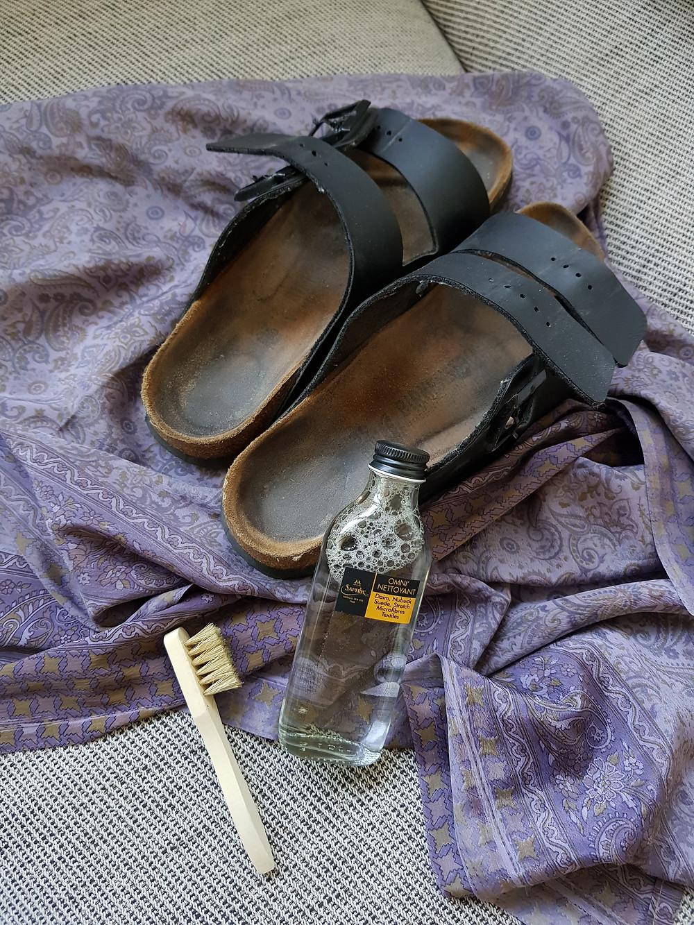 Kuvassa näkyy mokkakivellä kumitetut sandaalit lilan torkkupeiton päällä sekä pohjan pesuainepullo ja siihen kuuluva pieni harja.