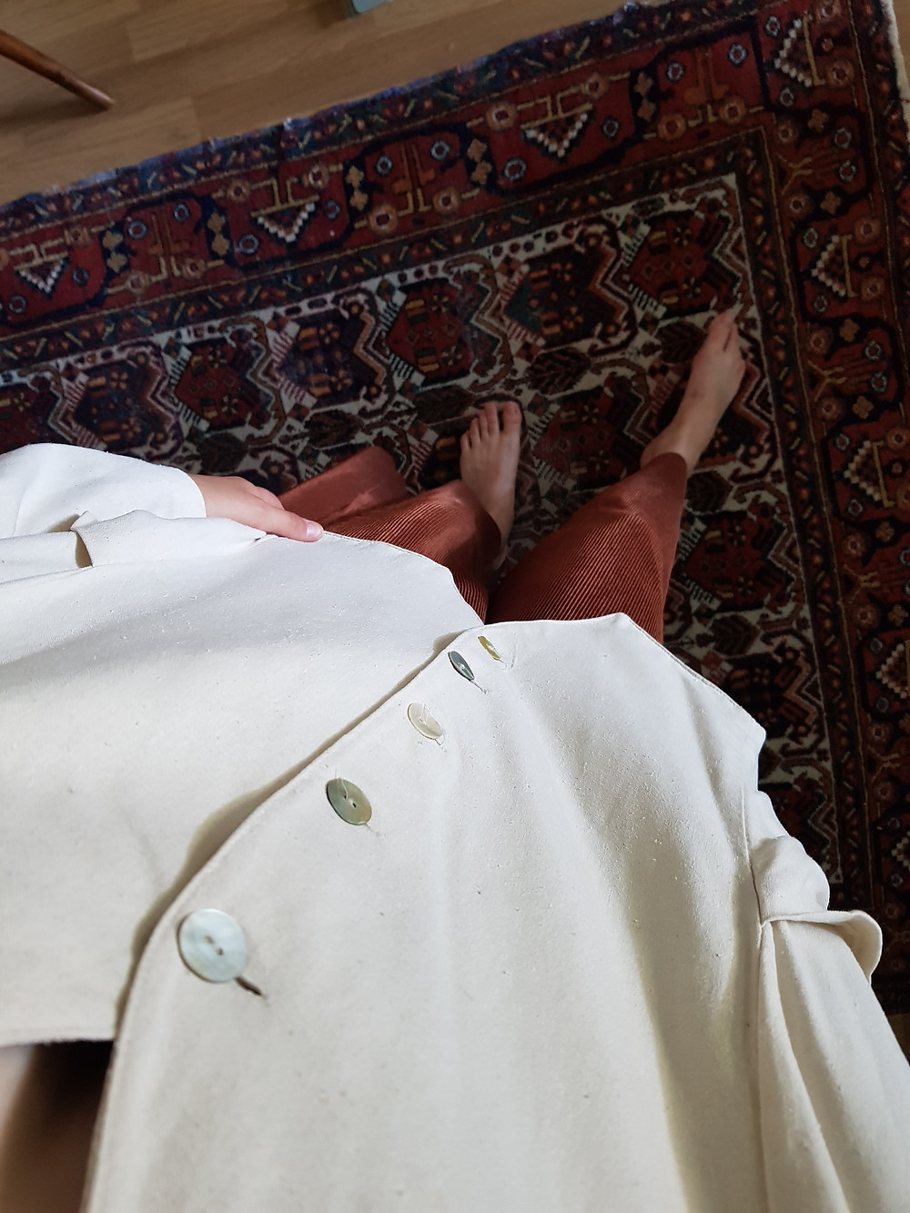Olen ottanut asukuvan ylhäältä alas kuvaten. Kuvassa näkyy munasävyinen itämainen matto ja päälläni on samat oranssit housut ja valkoinen bleiseri kuin edellisessä kuvassa.
