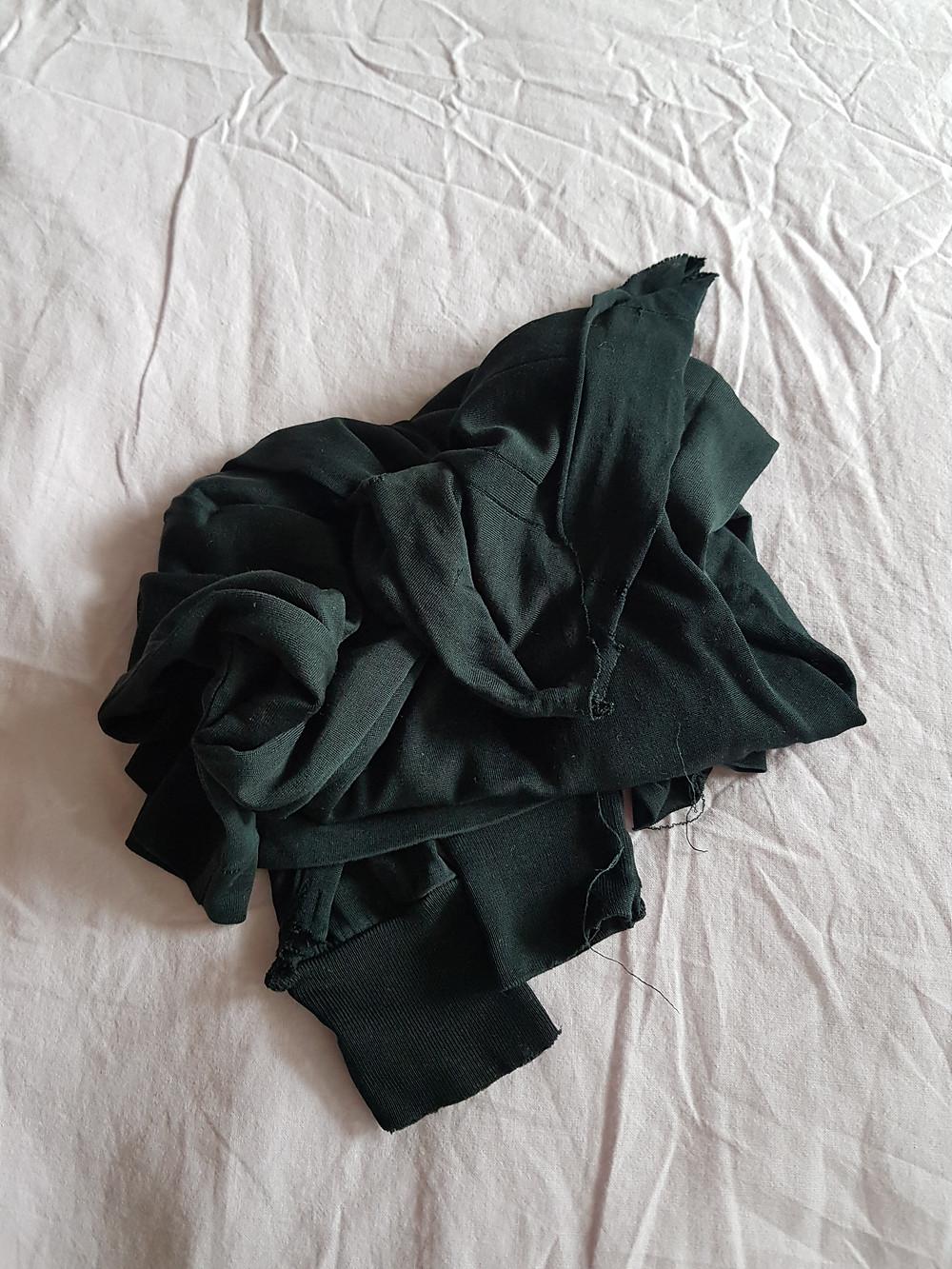 Musta silkkipaita rytyssä ryppyisen vaaleanliilan lakanan päällä.