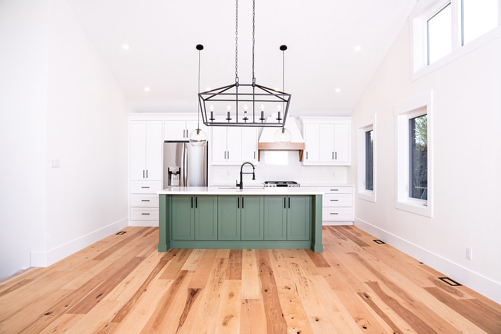 Bright white kitchen with wood floors and green island