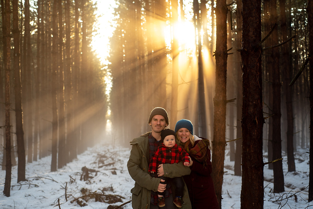 artistic family portrait of mom dad and son in forest