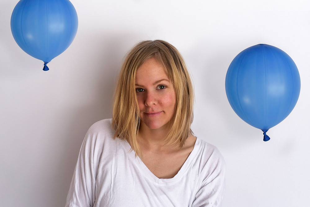Fine art self portrait for Hillary West Photography. Portrait of woman smiling on white background with a round blue balloon on either side.
