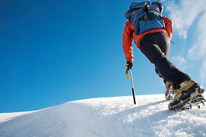 Lone male mountain climber climbing a sn