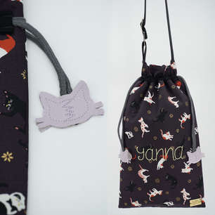 Crossbody bag with drawstring closure and cat head drawstring ends, personalised with hand embroidered name