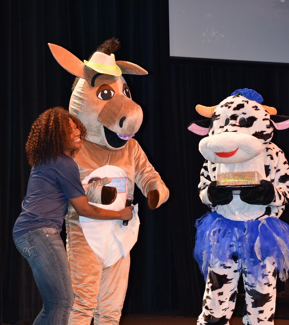 Ms. Jemima hugs Señor Burro as Madame Belle holds the birthday cake.