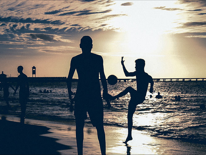people playing at beach sunset