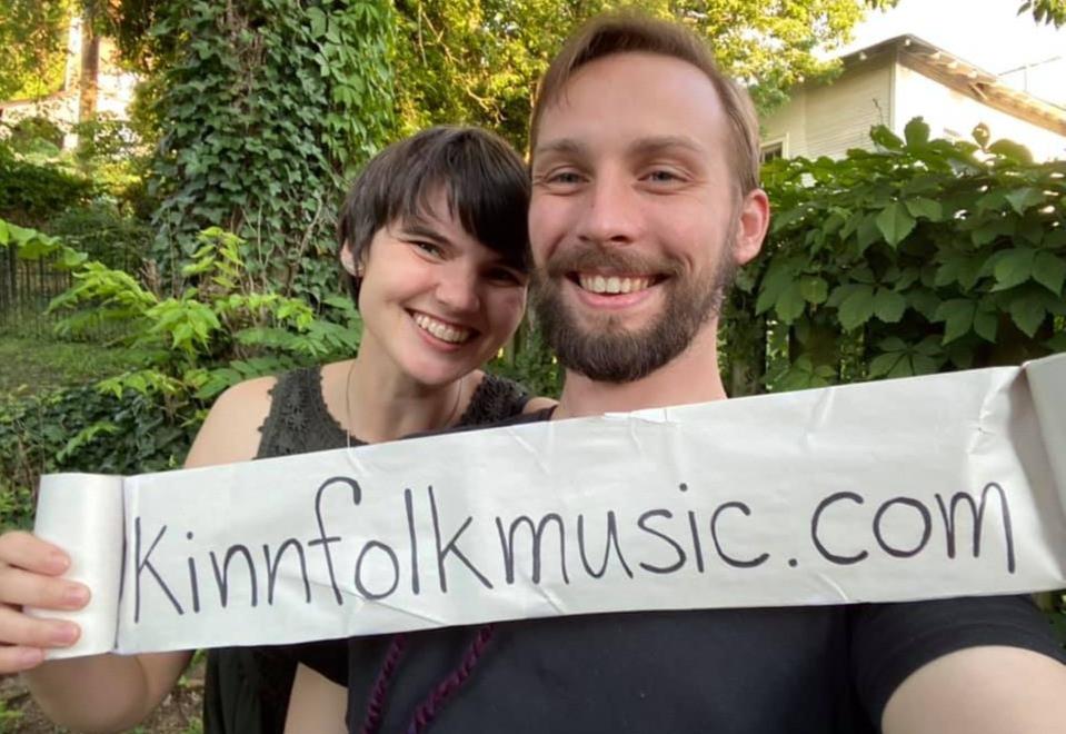 Kinnfolk hold a sign announcing their website