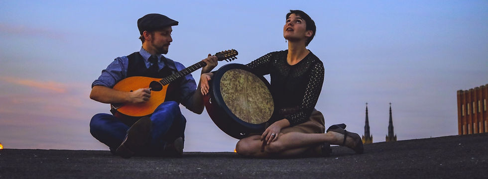 two folk musicians under twilight sky