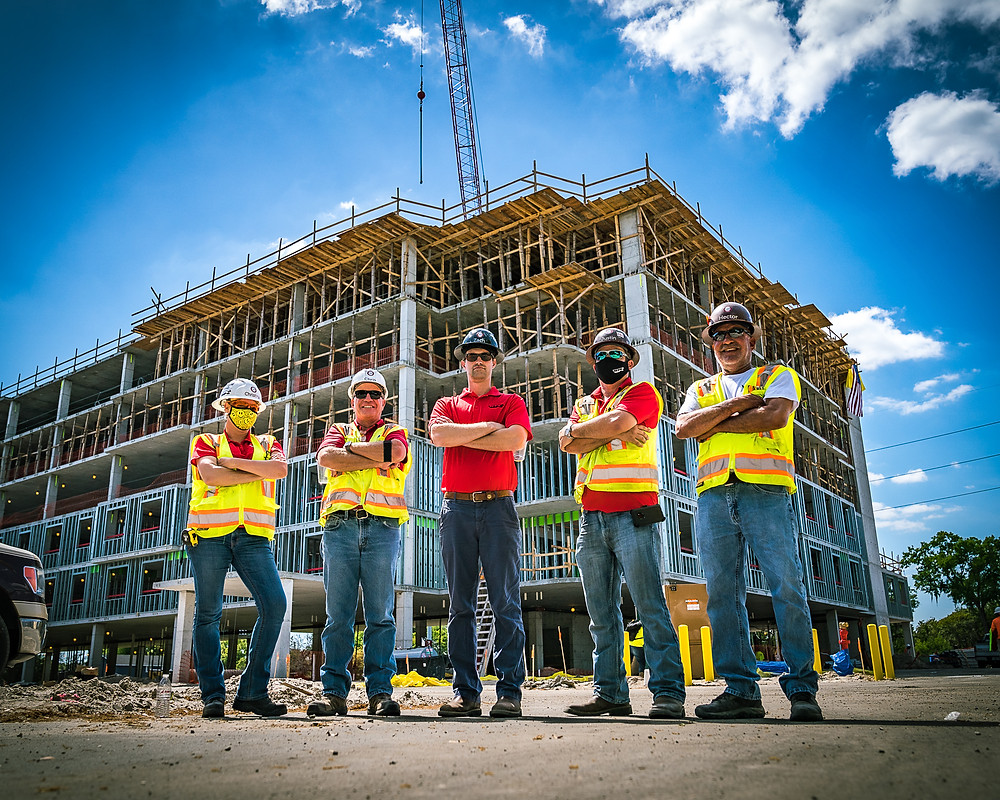 Construction crew with hard hats and yellow safety vests on the jobsite of an affordable senior housing project in Florida.