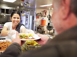 Woman serving meal at homeless shelter.j