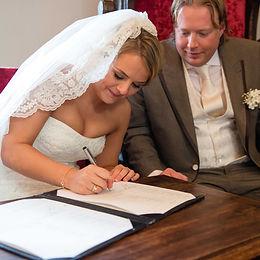 Trouwen, Bruidspaar tekent trouwakte, trouwbelofte, bruiloft, ceremonie, huwelijksceremonie, wettelijk huwelijk, tekenen trouwakte