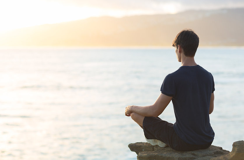 Young man meditating on top ocean cliff