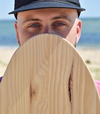 Portrait d'un homme regardant droit devant et se cachant le bas du visage avec le haut de son indoboard