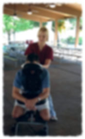 Kimberly giving a chair massage to a player before a golf tournament