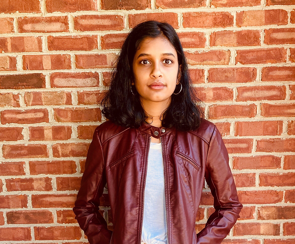 Gaia Rajan stands in front of a brick wall. She has dark shoulder length hair, and is wearing a white shirt and an auburn jacket.