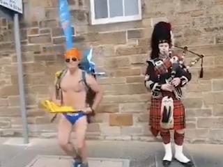 Fundraising hero Speedo Mick does Irish jig next to bagpiper at Edinburgh Castle during Giving Back Tour