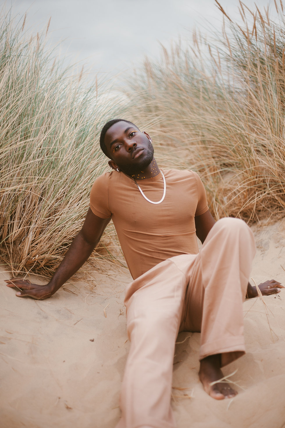 A man sitting on a sandy beach wearing brown clothes