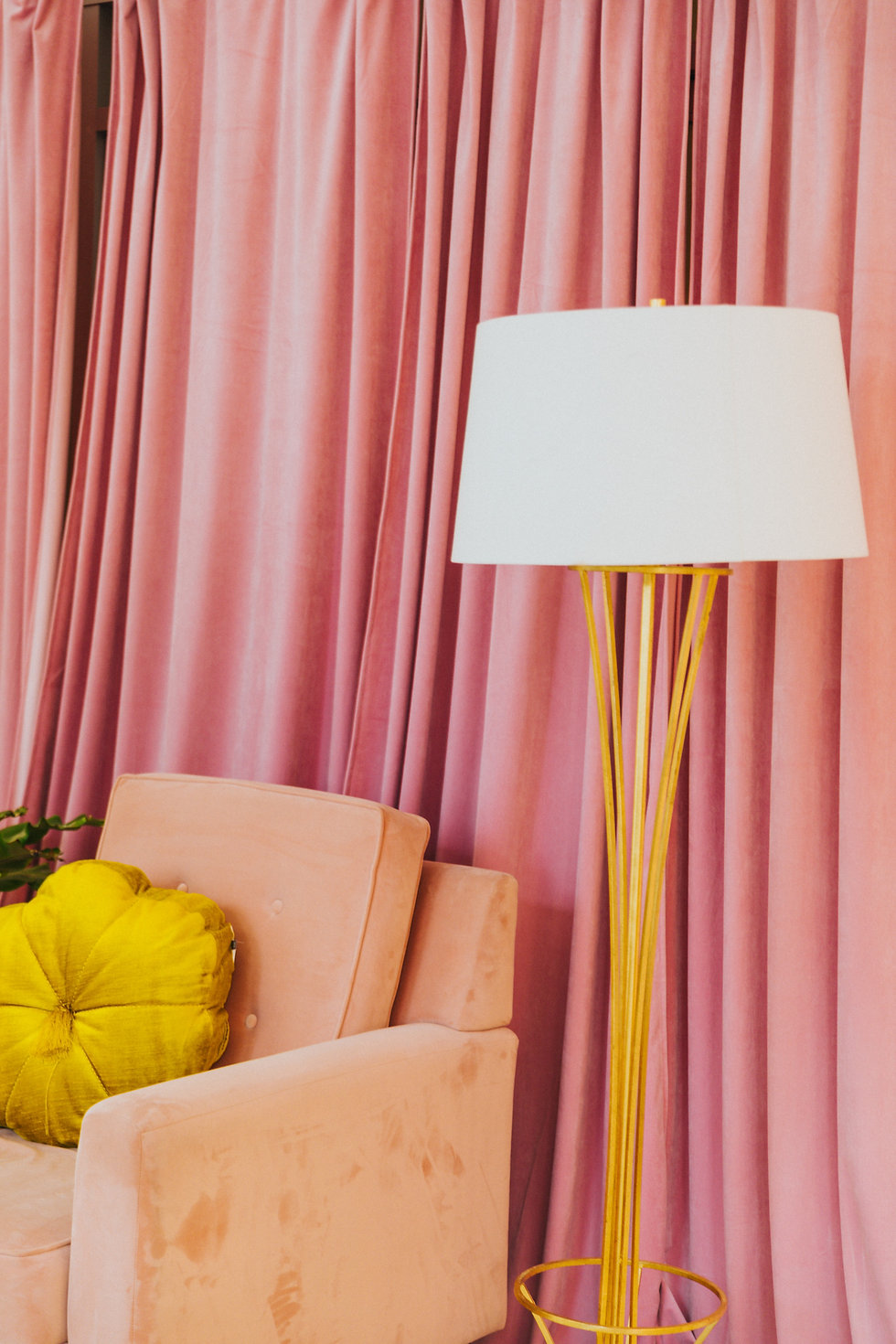 Peach armchair pink curtain and a yellow standing lamp