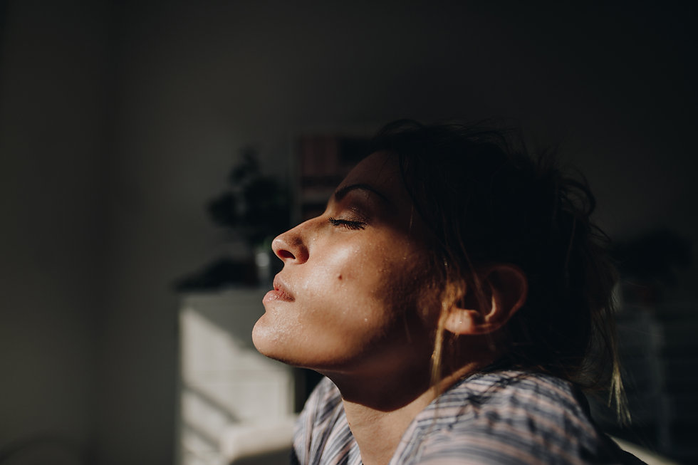 A portrait of a woman with eyes shuts facing the sunlight