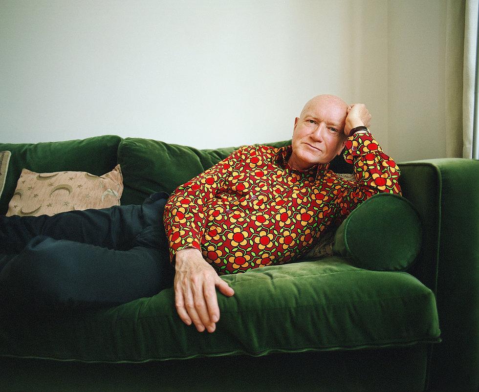 An older man is lying on a green velvet sofa
