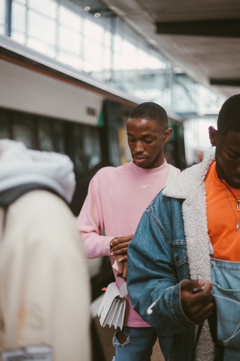 Two men standing in line in the Subway