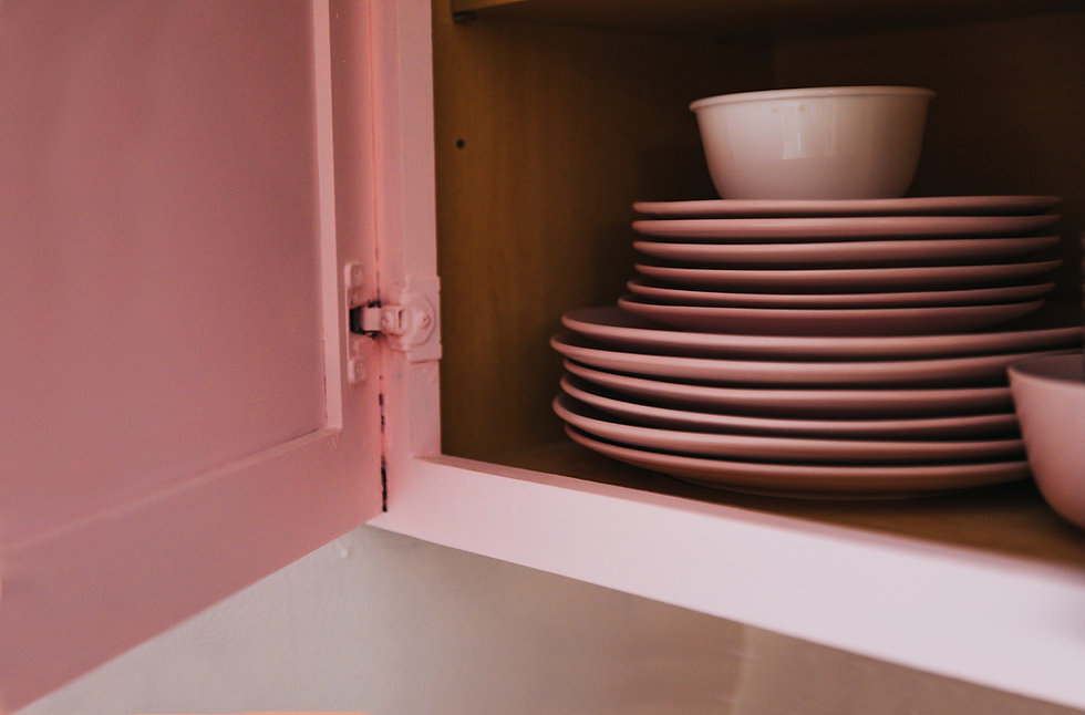 Pink ceramic dishes in a cabinet painted pink