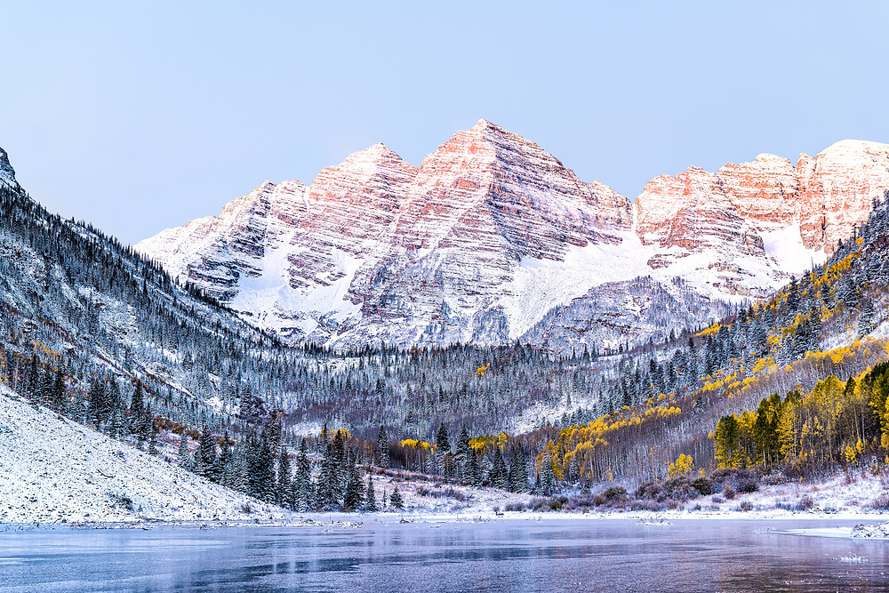 Maroon Bells morning sunrise with sunlight on peak in Aspen, Colorado rocky mountain and autumn yellow foliage view closeup and winter snow frozen lake