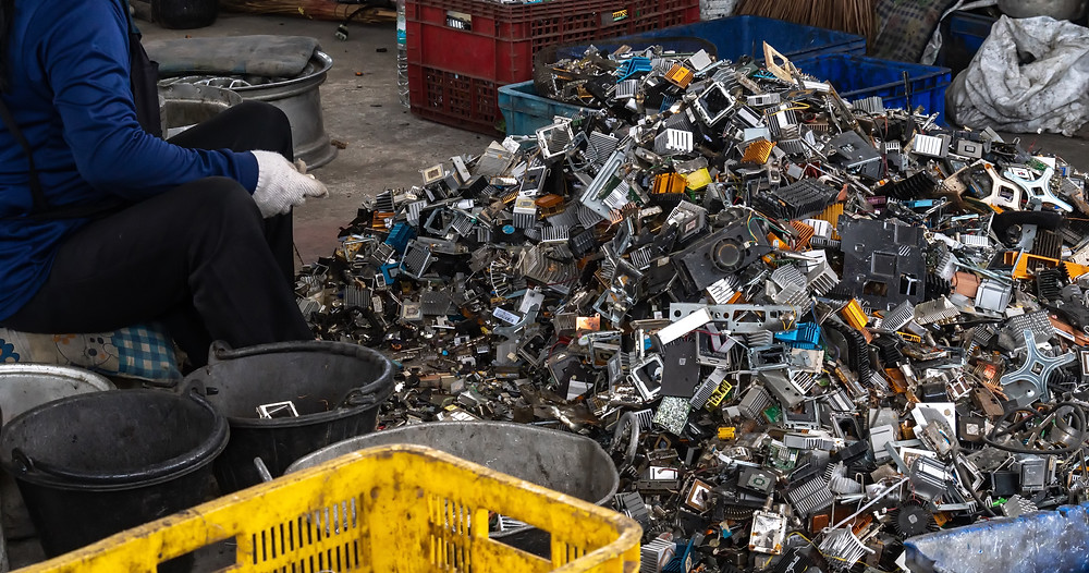 A person sorting through a pile of e-waste