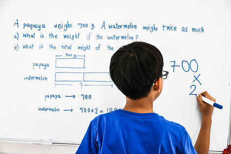 The Asian boy is solving word problem by