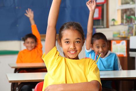 Three primary school children hands rais