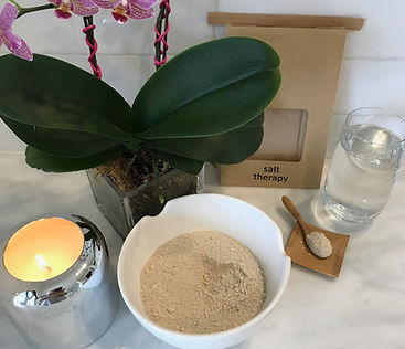 Salt and clay mix ready in a white bowl ready for salt therapy bath with candle, orchid and glass of water.