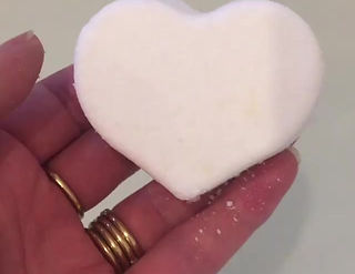 Adding a white bath bomb heart into a bath to see it fizz