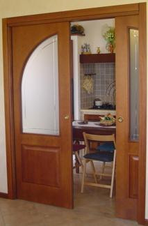 Porta scorrevole pantografata con vetro ovale