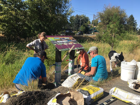 Project contributors install a large sign detailing the history of Missouri Flat Creek.