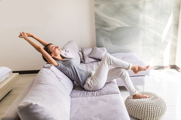 smiling-young-woman-relax-lying-couch.JP