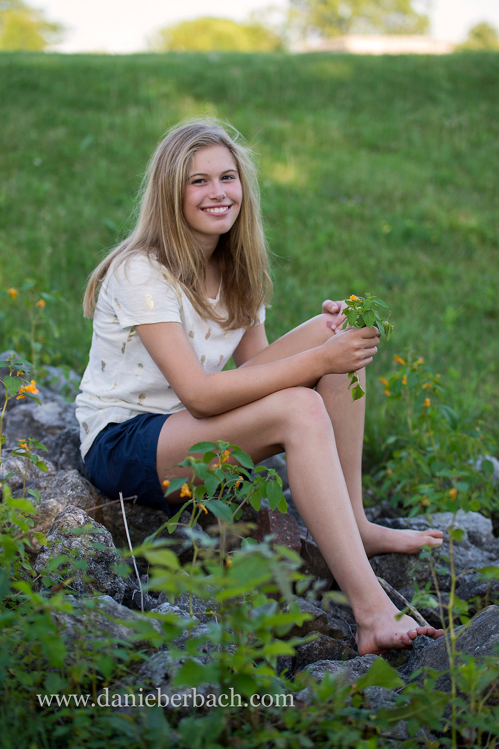 Young female portrait sitting outdoors with wildflowers