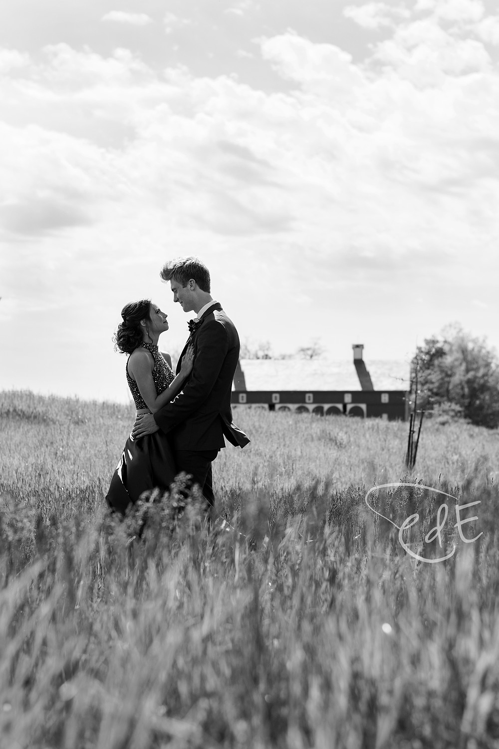 Black and white prom couple in grassy field