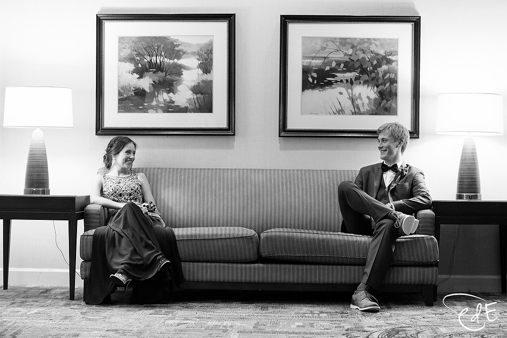 Couple in prom attire sitting on couch