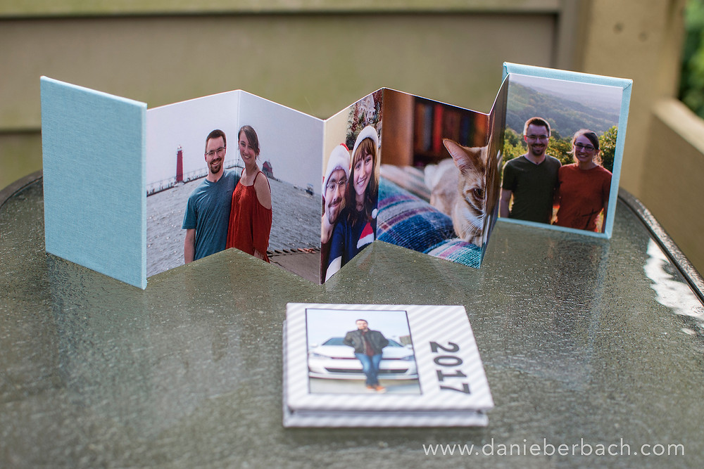 Wallet size mini accordion album standing on table